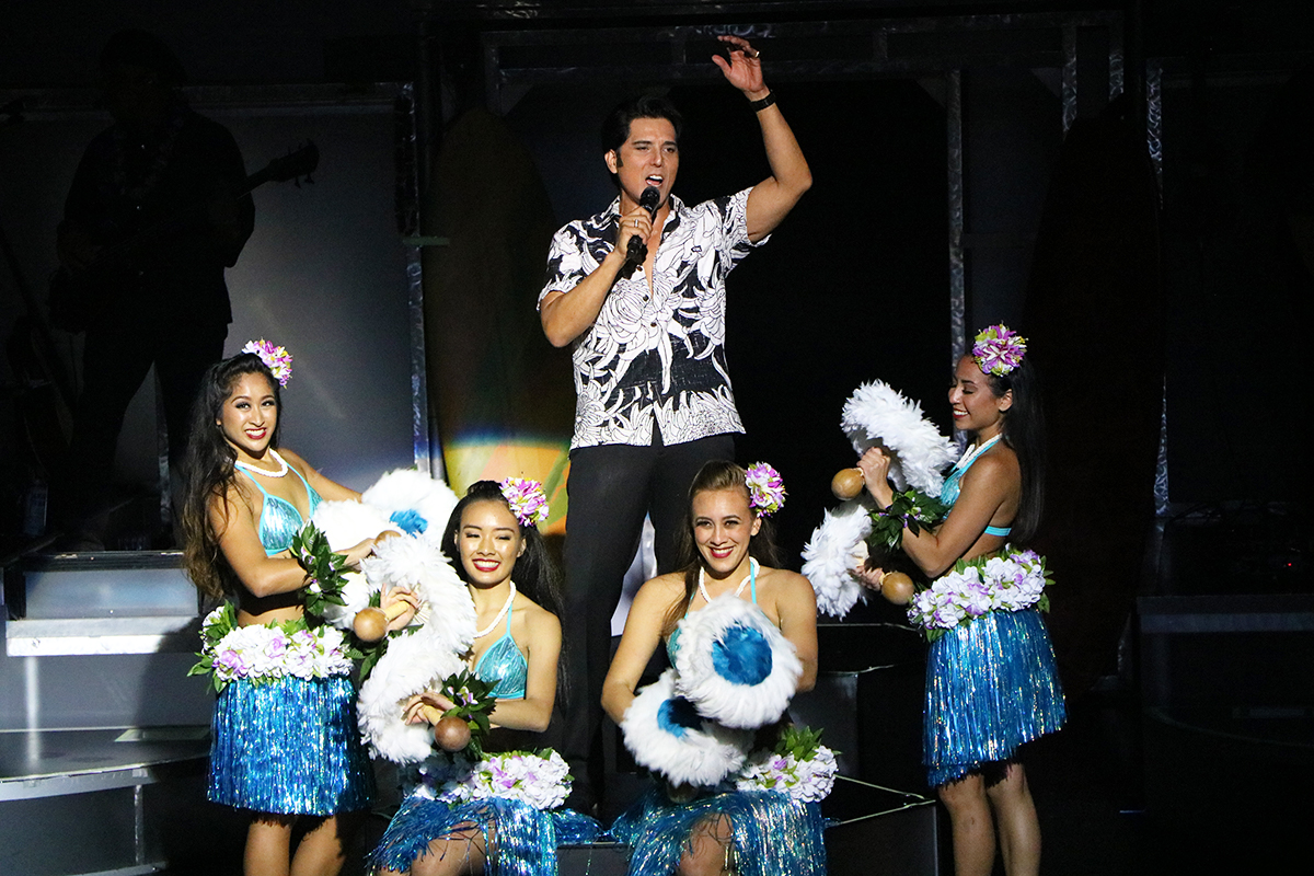 An Elvis impersonator surrounded by hula girls