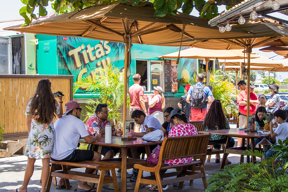 People eating outside of Tita's Grill food truck